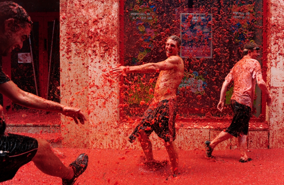 BUNOL, SPAIN - AUGUST 26: Revellers pelt each other with tomatoe pulp during the world's biggest tomato fight at La Tomatina festival on August 26, 2009 in Bunol, Spain. More than 45000 people from all over the world descended on the small Valencian town to participate in this year's La Tomatina festival, with the local town hall estimating that over 100 tons of rotten and over-ripe tomatoes were thrown. (Photo by Jasper Juinen/Getty Images)