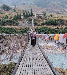 A man riding a bike on theseBhutanese bridge