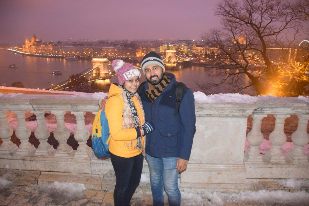 A couple posing with Budapest lit with lights as a background