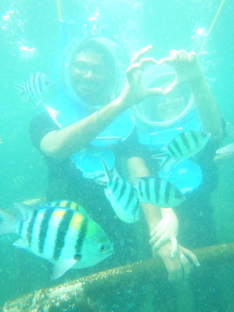 A couple showing the symbol of love during sea walking activity