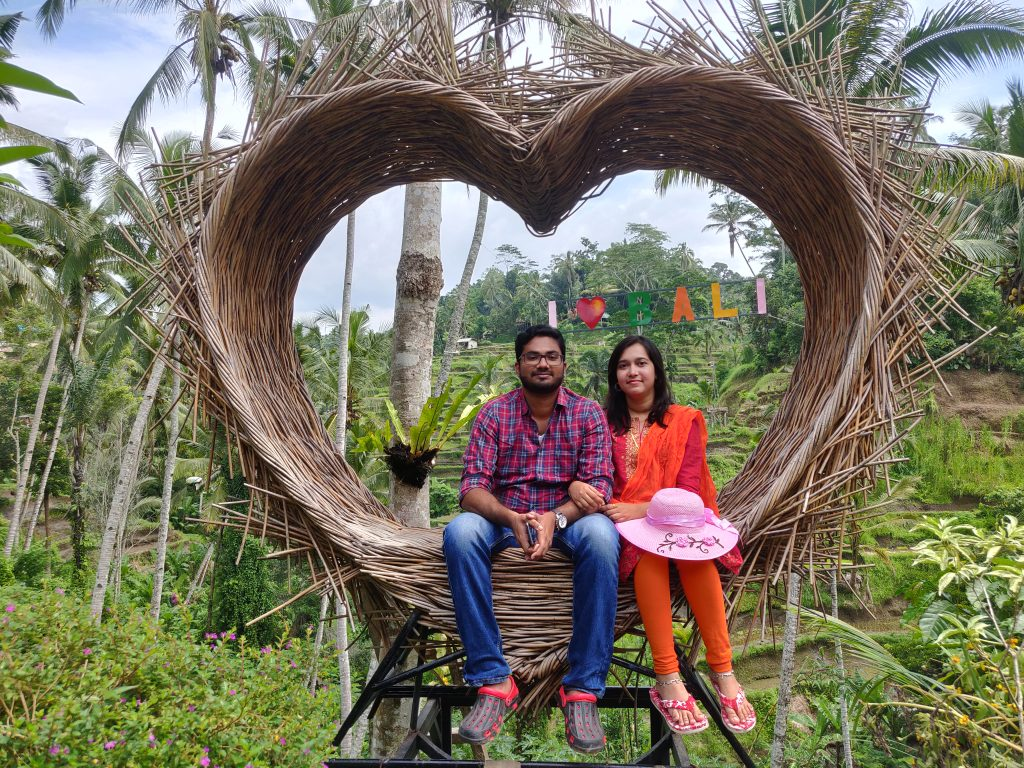 A couple posing with I love Bali sign as the background on their first international trip