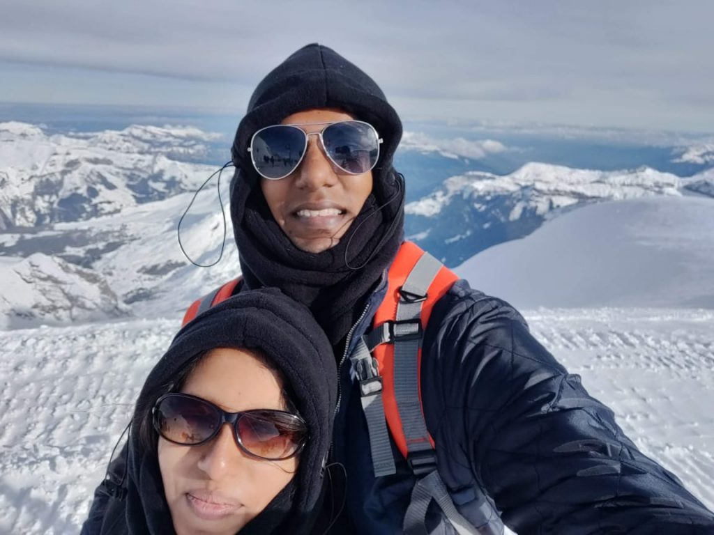 A couple posing in Europe with snow capped sorroundings