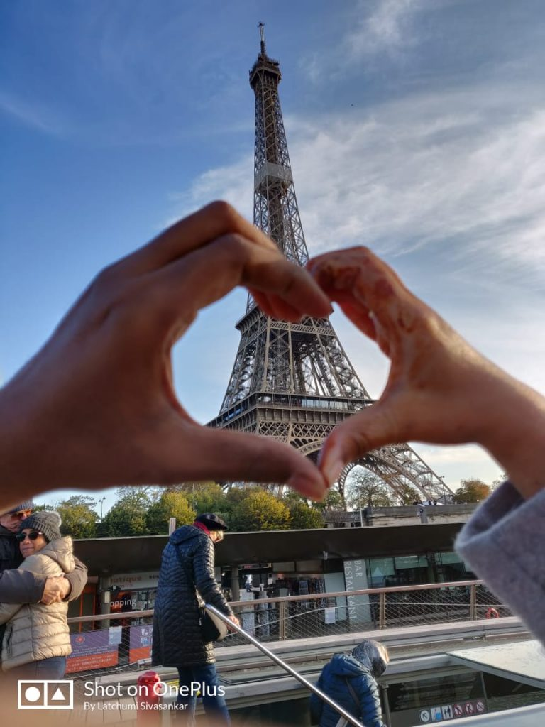 An amazing picture of a couple showing the symbol of love in Eiffel tower
