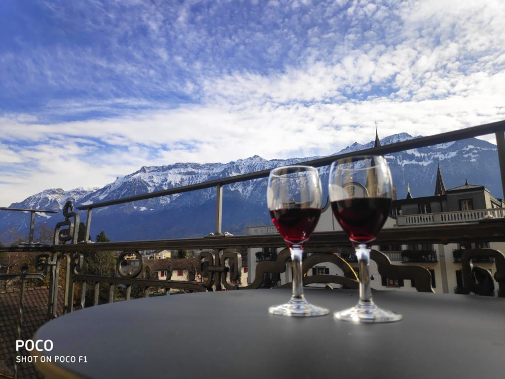 A pictures of two glasses kept on the table with beautiful skies above