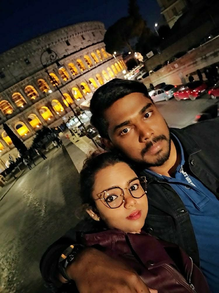 A picture of a couple taken in front of the colosseum in Rome