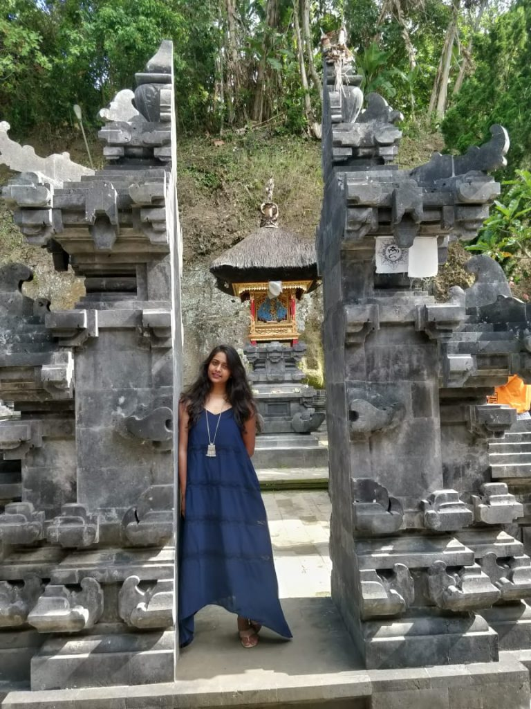 A picture of a lady standing in front of a temple