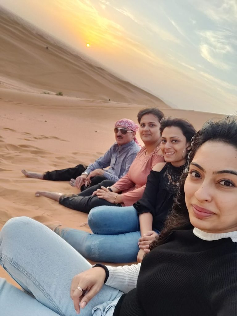 A group of people enjoy the sunset in the Desert Safari