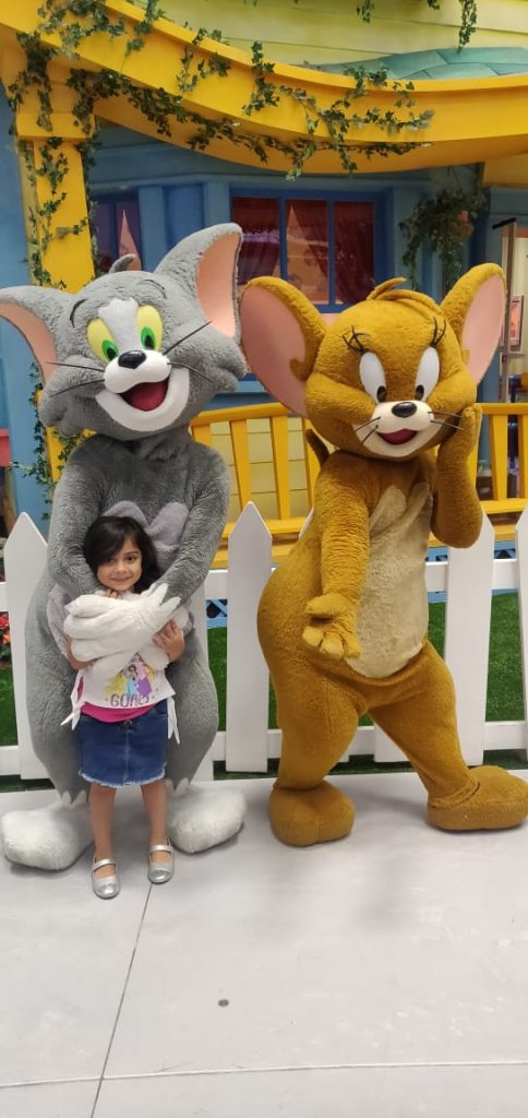 A picture of a cute little kid hugged by a mickey mouse on their family trip to Dubai