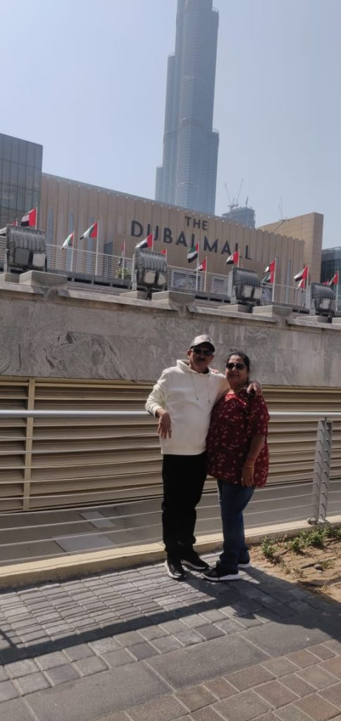 A couple posing for a picture in front of the Dubai Mall