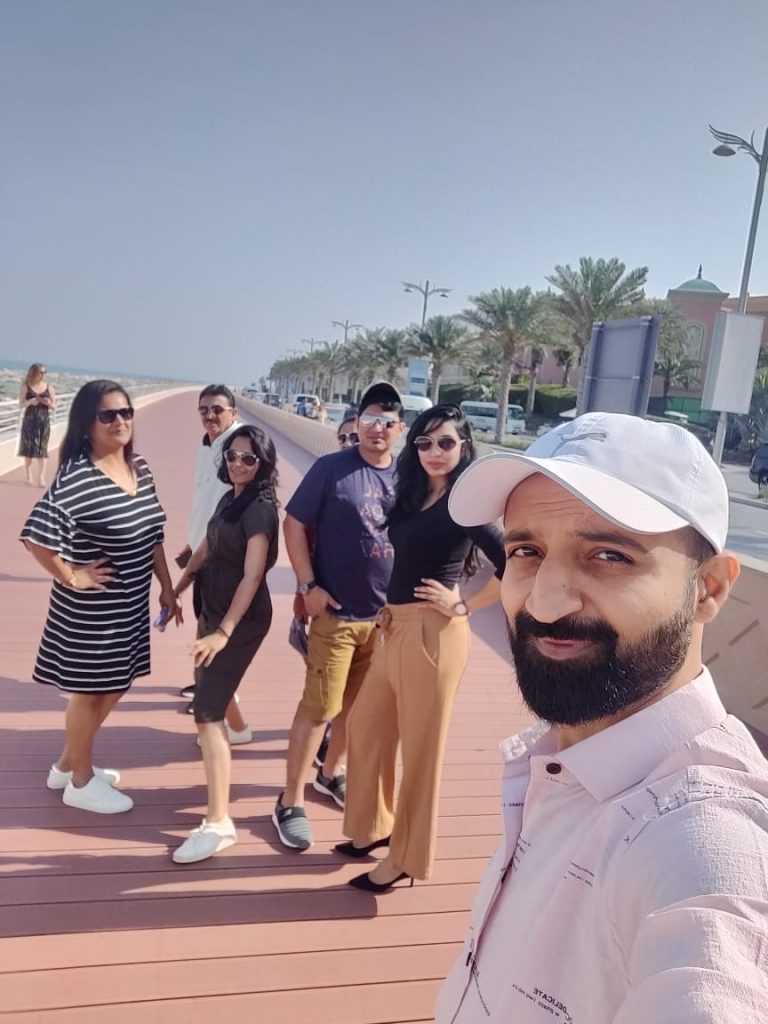 A group of people posing at the beach on their family trip to Dubai