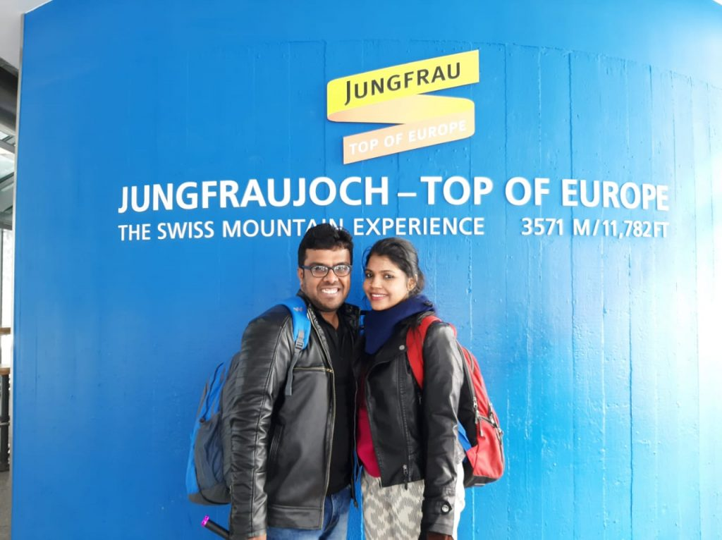 A picture of a couple posing at the Jungfraujoch on their honeymoon vacation to Europe