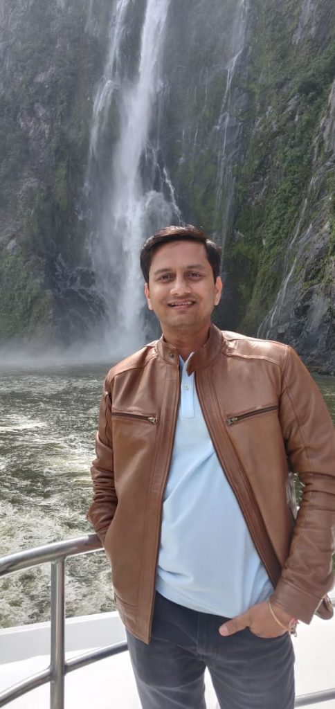 A man posing for a picture with waterfalls as the background
