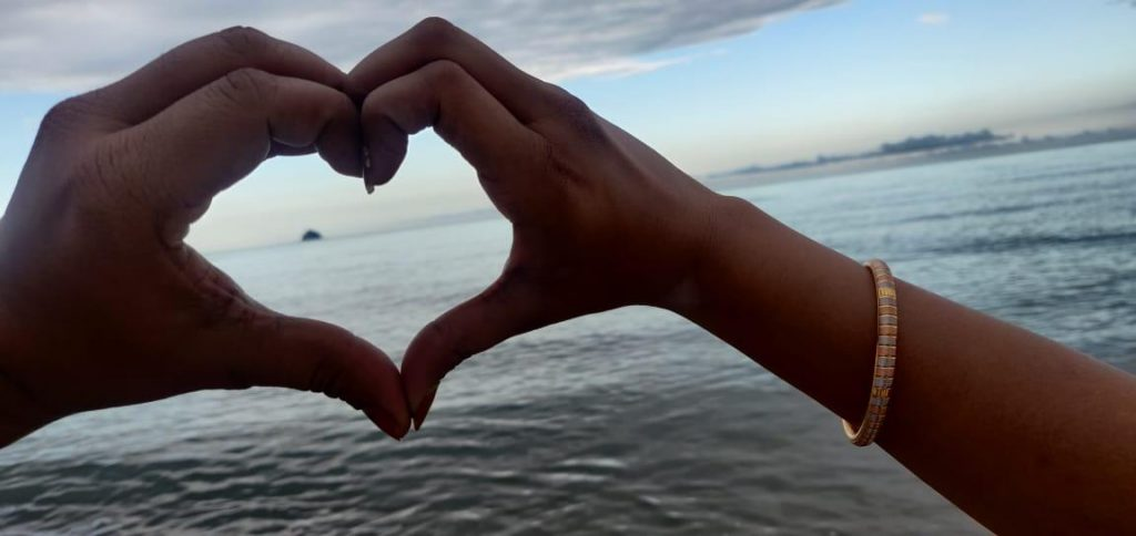 A couple showing the symbol of love on their honeymoon trip to Australia