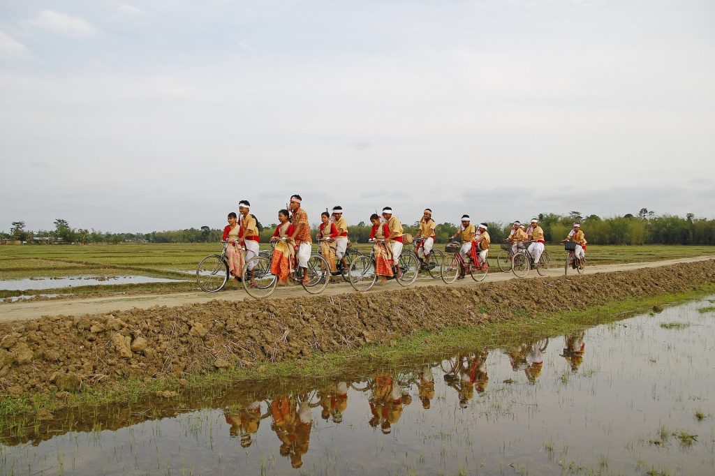 A group of people riding in bicylces in traditional clothes in one of the festivals of Assam
