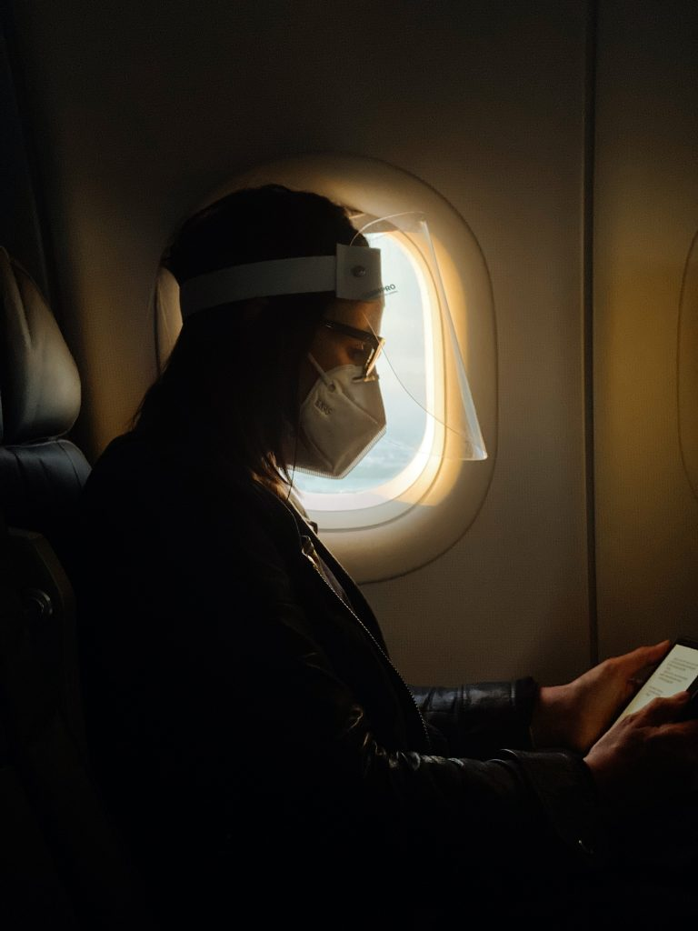 A lady sitting inside the flight, wearing a mask