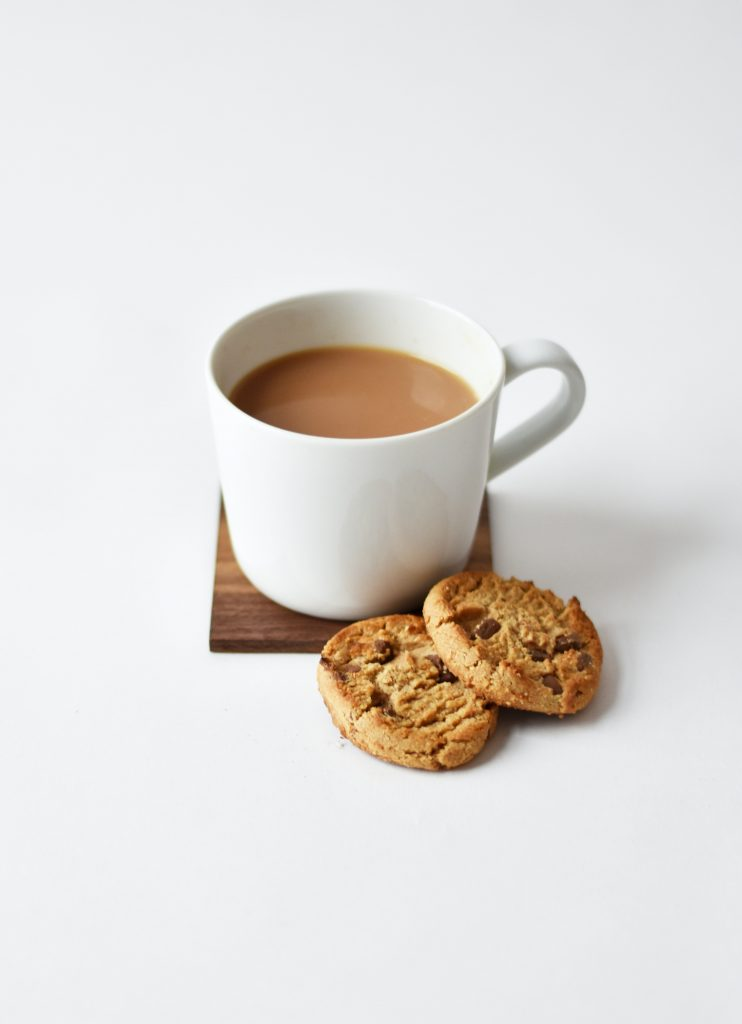 A cup of tea with 2 biscuits