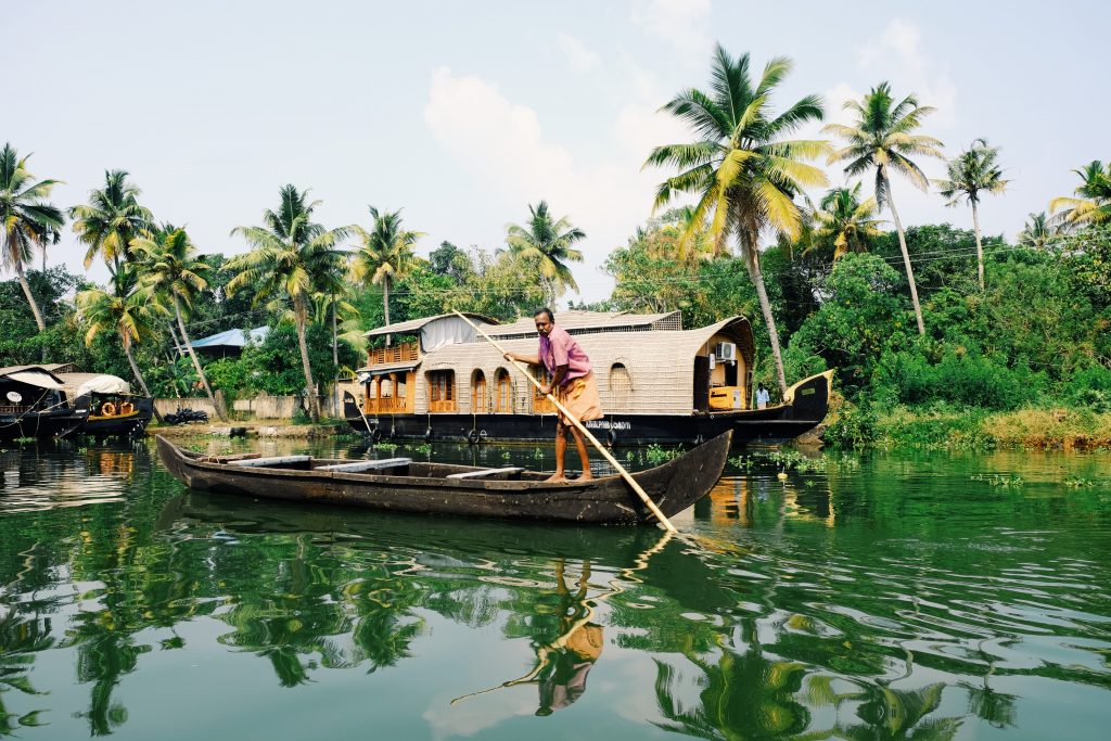 A picture of a man standing on a boat in Alleppey backwaters