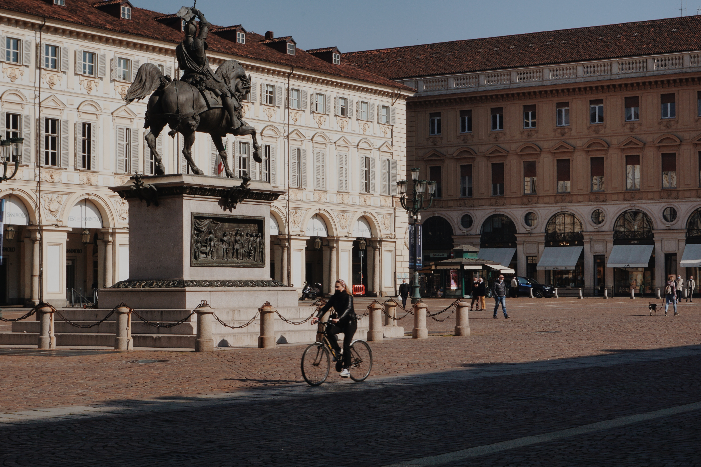 Woman riding a bike in Italian city, Torino, Italia