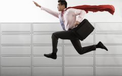 Businessman Wearing Cape --- Image by © Royalty-Free/Corbis
