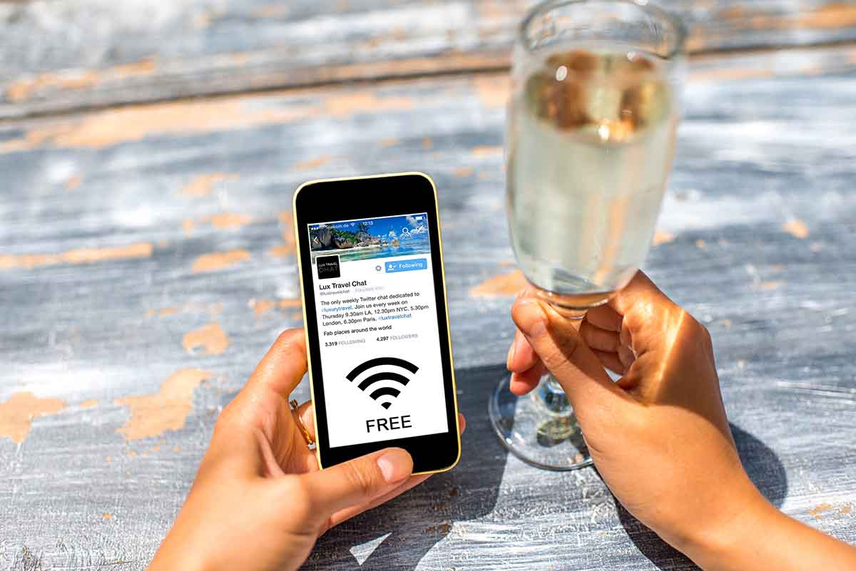 Female hand using a phone with isolated screen on wooden vintage table holding a goblet with champagne